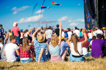 Teenagers, summer music festival, sitting in front of stage
