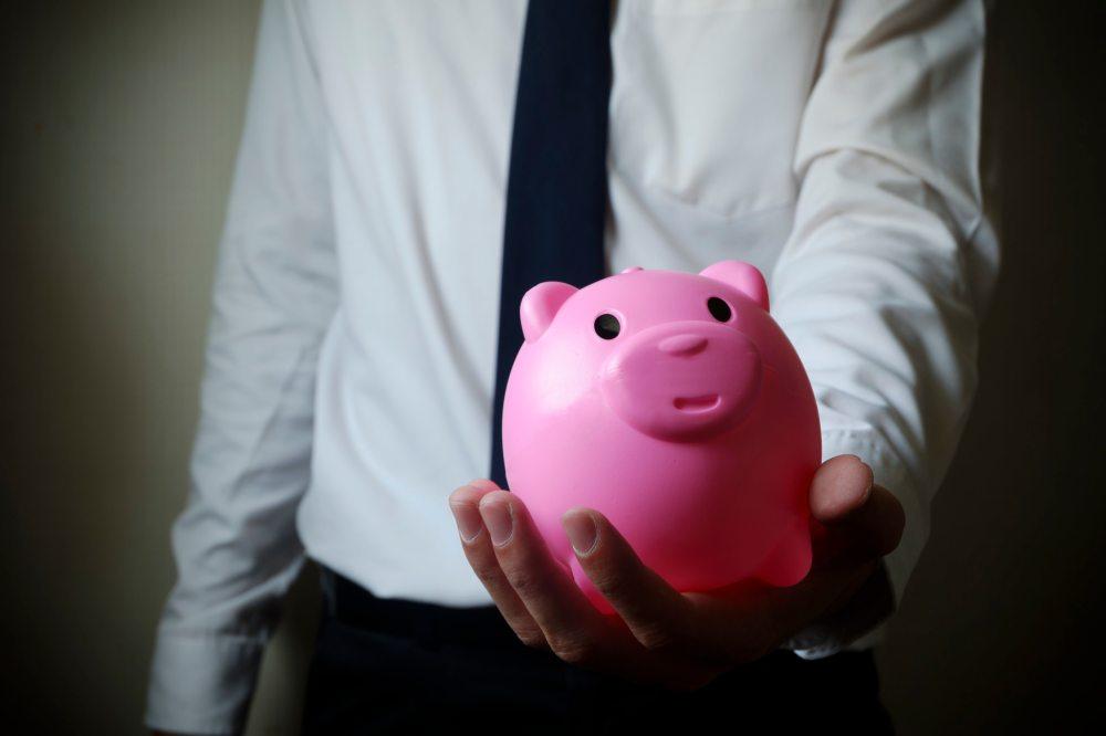 business man showing piggy bank , business finance concept